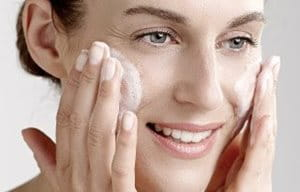 Woman applies cleansing gel on her face.